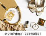 Small photo of Women's set of fashion accessories in golden color on wooden background: shoes, handbag, perfume and cosmetics