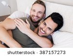 Happy Gay Couple Lying On Bed...