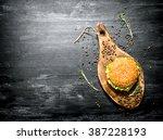 a hamburger on a wooden board....