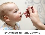 hungry baby has dinner from the ...   Shutterstock . vector #387239947