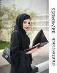 Small photo of Arab Business Woman in Black Abaya with a Folder