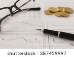 Small photo of pen ,glasses, money with the report analyzes stock market trends put on desk's fund manager. selective focus.