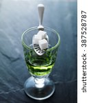 Small photo of absinthe in pontarlier glass with spoon and sugar cubes