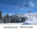 a chair lift transports skiers... | Shutterstock . vector #387611587