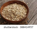 oats in a wooden bowl   rolled... | Shutterstock . vector #388414957