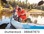 father and son rowing kayak on... | Shutterstock . vector #388687873