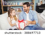 smiling daughter giving gift to ... | Shutterstock . vector #388697713