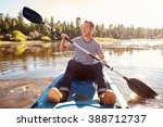 young man rowing kayak on lake | Shutterstock . vector #388712737