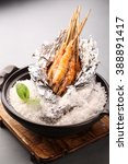 Small photo of Grilled prawns on a sticks covered in aluminium foil with salt