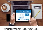 Small photo of Press Release concept on the tablet pc screen held by businessman hands, top view