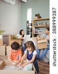family unpacking cardboard... | Shutterstock . vector #388999387