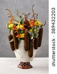 Small photo of Floral arrangement with cattail plant (acorus calamus), roses and freesias