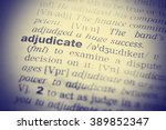 Small photo of Dictionary definition of adjudicate. Close up view with paper textures