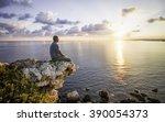 Man Watching Sunrise Sitting O...