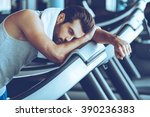 Small photo of Cannot run anymore. Side view of young man in sportswear looking exhausted while leaning on treadmill at gym