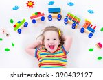 child playing with wooden train.... | Shutterstock . vector #390432127