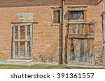 Small photo of Old wood doors on a brick building look like they were an afterthought or are covering spaces where nicer doors had once been.