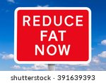Small photo of Red and white road sign REDUCE FAT NOW in front of blue sky, symbol for the health risks or dangers of overweight, spoof of british signposts