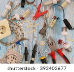 Small photo of energy-saving lamps are scattered in disarray, pliers, tools and electrical wiring on a blue background