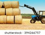 Tractor Unloads Bales Of Hay I...