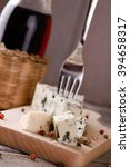 Small photo of Vertical askew photo of blue cheese portion placed on wooden board with colour pepper seeds around. Bottle of wine is next to cheese and small fork is stuck inside. All is on old grey table.