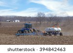Small photo of Farm tractor pulling anhydrous ammonia tanks fertilizing farmland