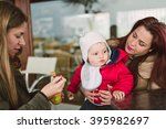 two women feeding baby food to... | Shutterstock . vector #395982697