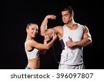 Small photo of Happy lady measuring bodybuilder's arm. Fitness couple on dark background. Sportsman satisfied with his progress. Girl proud of her man.