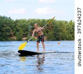 Small photo of Adventurous boy learning to paddle on stand up board. Happy child, teenage schoolboy, having fun enjoying adventurous experience on the river on a sunny day during summer holidays