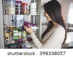 young woman picking a bottle... | Shutterstock . vector #398338057