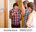 Small photo of Young couple having serious talking with angry neighbour at the door