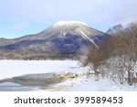 Small photo of Mount Akan, active volcano in winter with white snowcapped and foreground of frozen lake Akan and hot spring
