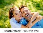 happy couple hugging  sitting... | Shutterstock . vector #400245493