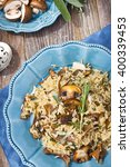 Small photo of Vegetarian risotto with mushrooms (porcini, baby bella and chanterelle) on wooden background