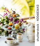 Small photo of Afternoon tea ceremony, beach restaurant with sea view, flowers orchids, cups, sweets, deserts, fruits