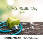 Small photo of World health day symbolic concept with map on healthy nutritional apple with doctor's stethoscope
