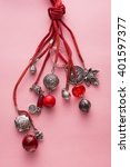 Small photo of High Angle Still Life View of Handmade Artisan Jewellery on Pink Background - Stylish and Funky Necklace Made with Red Leather and Adorned with Silver Charms and Red Beads and Stones