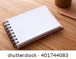 Spiral notebook with pencil on wood table