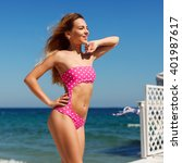 Small photo of Pretty young woman having fun on the beach in oink swimsuit