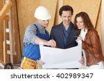 worker shows house design plans ... | Shutterstock . vector #402989347