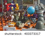 Small photo of ECHING, GERMANY - APRIL 3, 2016 - Stuff on display at open air spring flea market, helmets, globe, plush toys, figurines, frames, gas mask