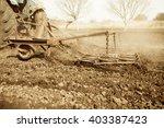 Tractor Plowing Soil On Farmland