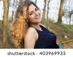 smiling curly girl in the park | Shutterstock . vector #403969933