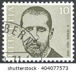 "Small photo of MOSCOW, RUSSIA - CIRCA APRIL, 2016: a post stamp printed in SWITZERLAND shows a portrait of Alexandre Yersin, the series ""Doctors"", circa 1971"