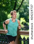 Small photo of Runner running listening to music with earbuds and fitness armband with workout app. Male athlete training during summer in urban New York city Central park sweating in sportswear activewear clothing.