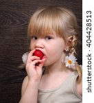 Small photo of Funny little girl eating a strawberry. Portrait, face close. Blond hair, pigtails. Strawberries ripe, red. Girl grubby and rather