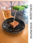 Small photo of Small pieces of nama (fresh) chocolate on black plate served with hot tea on wooden table - inside nice coffee shop area