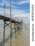 Small photo of Wooden jetty for fishing in the Gironde Medoc France with blue sky and white clouds.