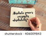 Small photo of Retro effect and toned image of a woman hand writing on a notebook. Handwritten quote Absolute power corrupts absolutely as inspirational concept image