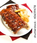 Ribs with smoky spicy sauce accompanied by french fries - stock photo